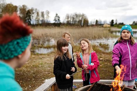 Luonto-ohjaaja Anna Salonen (vas.) seuraa, kun Peppi Helenius, Viljo Kudjoi, Paju Mäkihannu ja Matilda Mikkola paahtavat vaahtokarkkeja koulun retkipaikalla.