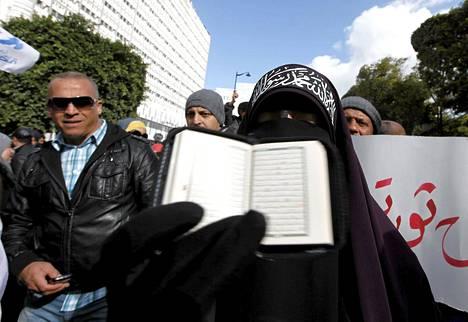 Koraania kädessään pitävä nainen osoitti mieltään Tunisissa lauantaina.