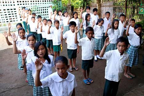 """Casilin ala-asteen oppilaat lausuivat """"Panatang Makabayanin"""", uskollisuudenvalan Filippiineille, ennen koulupäivän alkua Filippiinien Montalbanissa Manilan pohjoispuolella."""