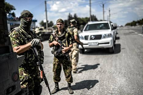 Ukrainan sotilaat vartioivat lähellä Etyjin saattuetta sen kulkiessa malesialaiskoneen putoamispaikalle torstaina.