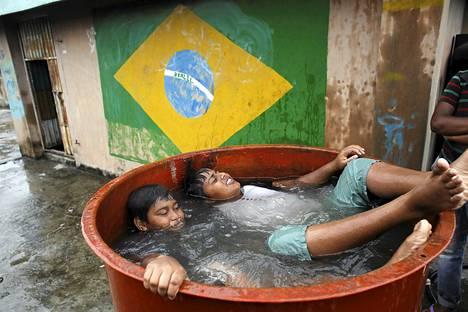Lapset kylpivät vesitynnyrissä Dhakassa Bangladeshissa. Maa valmistautuu seuraamaan jalkapallon MM-kilpailuja ja monet kannustavat joko Brasiliaa tai Argentiinaa.