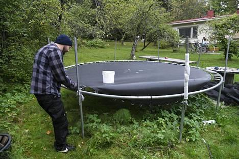 Mies purki trampoliinia talonsa pihalta lähestyvän syysmyrskyn varalta Helsingissä keskiviikkona.