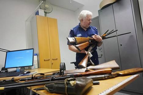 Ylikonstaapeli Ilari Vilén tarkasteli palautettuja aseita Pasilan poliisitalolla. Pasilaan palautettujen aseiden määrä on kasvanut.