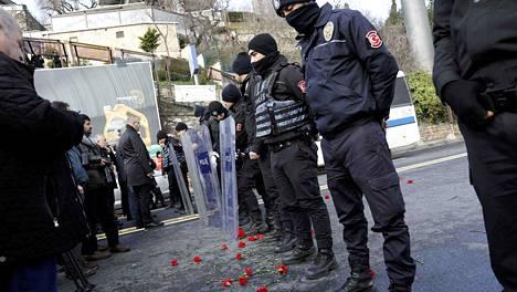Yökerhoiskun uhreja surevat ihmiset toivat punaisia neilikoita tapahtumapaikkaa vartioivien poliisien jalkoihin.