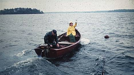 Saareen kuljettiin kesäisin pienillä veneillä oli ilma mikä hyvänsä. Veneen kyydissä Dahlmanien mökkinaapurit Alli ja Bror Backman.