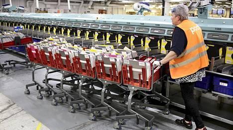 Postin lajittelukeskus Pasilassa käsittelee noin 65–70 prosenttia koko maan postilähetyksistä. Kuvassa postityöntekijä Leea Nuutinen työskentelee kirjeiden ja lehtien lajittelukoneella.