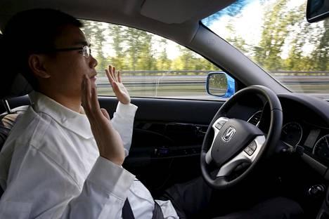 Saksan parlamentin hyväksymän lain mukaan kuljettajan pitää istua jatkuvasti itsestään ajavan auton ratin takana valmiina ottamaan auto hallintaansa tarpeen vaatiessa. Kuvassa Changan Automobilen kehitysinsinööri Li Zengwen koeajaa itsestään ajavaa autoa Pekingissä huhtikuussa 2016.