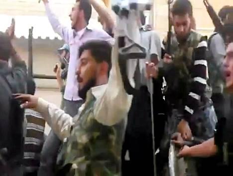 Youtube-videopalveluun lähetetystä videosta otettu kuvakaappaus näyttää Syyrian kapinallisjoukkojen kulkevan Aleppon kaupungin läpi tankin päällä.