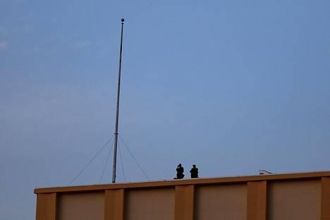 Poliisin tarkka-ampujaryhmä tarkkaili kynttilämuistotilaisuutta poliisiampumisten jälkeisenä maanantaina Dallasissa.