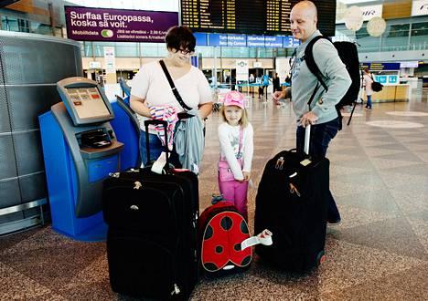 """Heidi Kaarla-Lauhiala (vas.), Tipi ja Mark Lauhiala odottelivat perjantaina Espanjan loman jälkeen jatkolentoa Kajaaniin. """"Käytämme noin 60 euroa lisäpalveluihin lentoa kohden"""", Heidi Kaarla-Lauhiala harmittelee."""