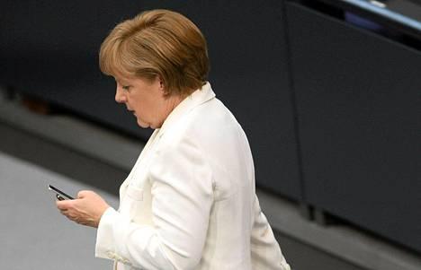 Liittokansleri Angela Merkel tutki puhelintaan parlamentissa Berliinissä kesäkuussa 2012.