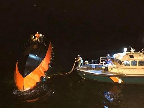 Merivartioston sukeltajat yrittivät kääntää luotsivenettä perjantaina. Vartiolaiva Turva antoi operaatiolle suojaa tuulelta.