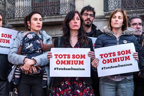 """Vangitun Jordi Cuixartin vaimo Txell Bonet (vas.) piteli lastaan kantorepussa mielenosoituksessa Barcelonassa maaliskuussa. Kylttien teksti """"Me kaikki olemme Òmnium"""" viittasi Òmnium Cultural -kansalaisjärjestöön, jota Cuixart johtaa."""