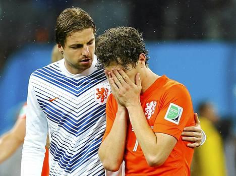 Hollannin maalivahti Tim Krul lohduttaa Daryl Janmaatia hävityn Argentiina-välierän jälkeen.