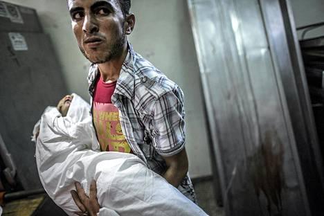 Sukulainen kantoi Israelin tulituksessa kuolleen kaksivuotiaan Salma Radiyan ruumista Kamal Adwanin sairaalassa Gazassa keskiviikkona.