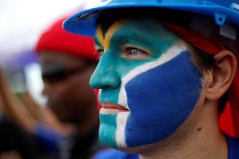 Etelä-Afrikan presidentin Jacob Zuman eroa vaativa mielenosoittaja Durbanissa on maalannut kasvoihinsa maansa lipun värit.