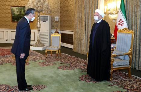 Kiinan ulkoministeri Wang Yi (vas.) kävi tervehdyskäynnillä Iranin presidentin Hassan Rouhanin luona ennen yhteistyösopimuksen allekirjoitustilaisuutta.