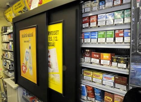 Savukkeita liukuovellisissa tupakkakaapeissa Fredrikinkadun R-kioskissa Helsingissä.