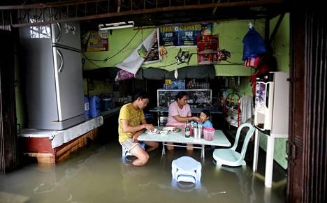 Paikalliset söivät monsuunisateiden jäljiltä tulvivassa ravintolassa Manilan pohjoispuolella Masantolissa.
