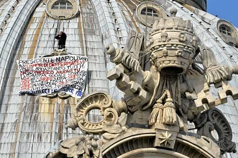 Kahvilanpitäjä Marcello Di Finizio osoitti mieltään Pietarinkirkon kupolin päällä maanantaina.