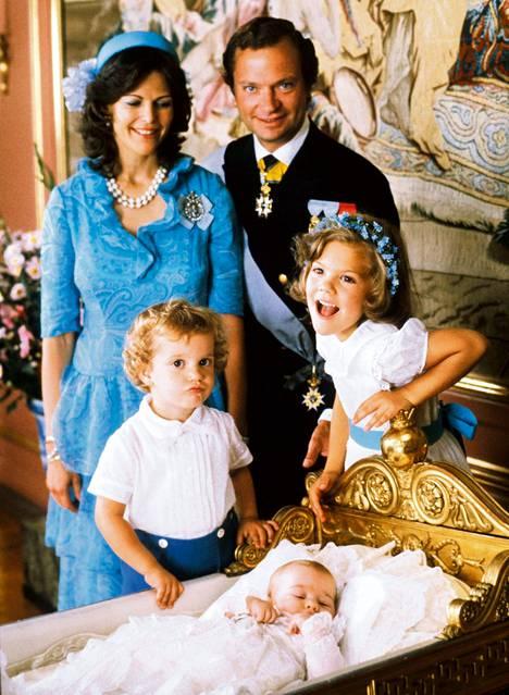 """""""Tässä olemme koolla Linnankirkossa järjestettyjen prinsessa Madeleinen kastajaisten jälkeen. Seisomme vastaanotolla Loviisa Ulriikan audienssihuoneessa linnassa. Muistan selvästi, kuinka me aikuiset katsoimme hetken toisaalle ja kääntäessämme katseemme taas takaisin näimme kruununprinsessan ja prinssi Carl Philipin heiluttavan väkivaltaisesti kehtoa, jossa prinsessa makasi. Oli tuuria, ettei kukaan tai mikään vahingoittunut"""", kirjoittaa Ruotsin kuningas kirjassa, johon on koottu valokuvamuistoja 40-vuotiselta uralta."""