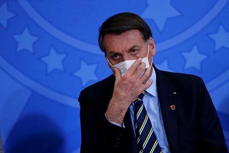 Brasilian presidentti Jair Bolsonaro asetteli suojamaskiaan uuden viestintäministerin Fabio Farian virkaanastujaisissa 17. kesäkuuta 2020.