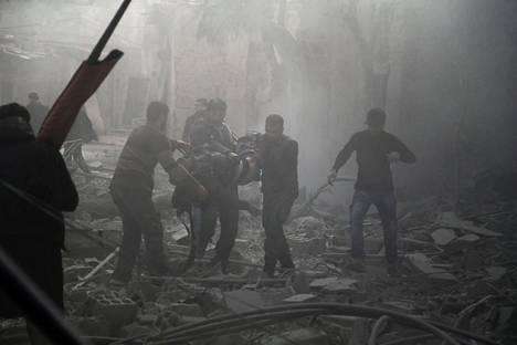 Vapaaehtoiset pelastustyöntekijät kantoivat ilmaiskussa loukkaantunutta siviiliä Saqbassa saarretulla Itä-Ghoutan alueella Damaskoksen lähistöllä tiistaina.