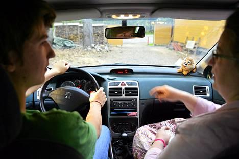 Minna Söderqvist opettaa poikaansa Karia ajamaan autoa.