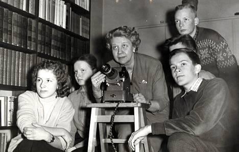 Yhdistetty radio-rainaopetus aloitettiin kouluradiossamme v. 1952 ensimmäisenä pohjoismaista. Ensimmäisessä värirainan avulla havainnostetussa lähetyksessä oli aiheena Eero Järnefeltin taide, jota prof. Aune Lindström (kuvassa kesk.) esittelee.
