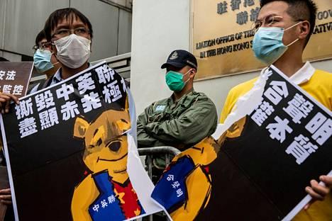 Turvallisuuslakien vastustajat kantoivat Nalle Puhin kuvalla varustettuja kylttejä viikonloppuna Kiinan yhteystoimiston lähistöllä sunnuntaina. Puh symboloi Kiinassa presidentti Xi Jinpingiä.