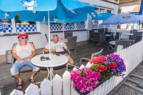 """2020: Iiläiset Mika Hast ja Pekka Suopanki nauttivat janojuomaa Jäppisen baarissa Iissä perjantaina. """"Helteethän tuntuu hyvältä, mutta sääskiä on paljon"""", Suopanki kertoi. """"Loska kesäkuu on ollut hyvä, niin heinäkuu on varmasti kylmä. Peruspessimistille heinäkuu ei voi olla hyvä."""""""