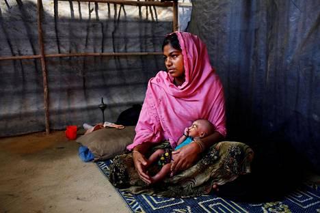 Asmot Ara, 18, piti sylissä seitsemän päivän ikäistä vielä nimeämätöntä tytärtään Balukhalin pakolaisleirissä Myanmarissa helmikuussa. Ara saapui pakolaisleiriin lapsensa ja naapureidensa kanssa sen jälkeen kun Myanmarin armeijan joukot tappoivat hänen isäpuolensa ja polttivat heidän talonsa.
