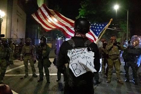 Mielenosoittaja heilutti Yhdysvaltain lippua liittovaltion joukkojen edessä 30. heinäkuuta. Joukkojen läsnäolo on herättänyt Portlandissa laajaa vastustusta ja protestointi joukkojen tultua on jopa yltynyt.
