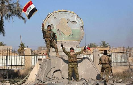 Irakin joukkojen sotilaat poseeraavat takaisin valtaamassaan Ramadissa 28. joulukuuta.