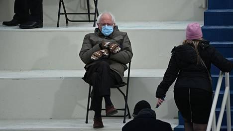 Kuva, josta meemit syntyivät. Entinen presidenttiehdokas ja Vermontin senaattori Bernie Sanders istumassa avokatsomossa Capitol Hillissä ennen kuin Joe Biden vannoi valansa Yhdysvaltojen 46. presidenttinä.