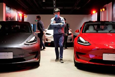 Potentiaaliset asiakkaat kävelivät maskit yllään Teslan esittelytiloissa Shanghaissa toukokuussa.