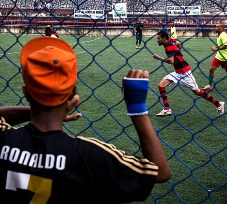 Poika katselee jalkapallopeliä Copa Popular -kisoissa, jotka järjestettiin Morro do Salgueiron favelassa Rio de Janeirossa.