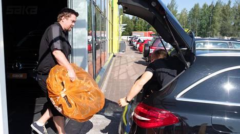 PTT:n mukaan autokauppa on piristymässä Suomessa. Kuvassa asiakas kantaa talvirengasta Sakan Konalan myymälästä ostamaansa käytettyyn Mersuun heinäkuussa.