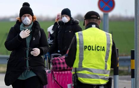 Hengityssuojaimin varustautuneet ihmiset yrittivät ylittää rajaa Itävallasta Slovakiaan perjantaina. Slovakia päätti perjantaina sulkea rajansa kaikilta muilta ulkomaalaisilta paitsi puolalaisilta.