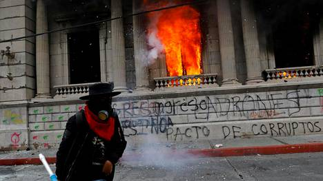 Presidentti Alejandro Giammattein eroa vaativat mielenosoittajat sytyttivät kongressirakennukseen tulipalon Guatemala Cityssä lauantaina.