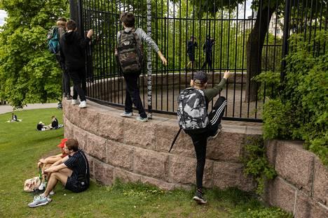 Sinebrychoffin puistossa oli perjantaina päivällä paljon lapsia leikkimässä. Muuria vasten istuvat Eromon Agbomeirele ja Niklas Kuikanmäki.