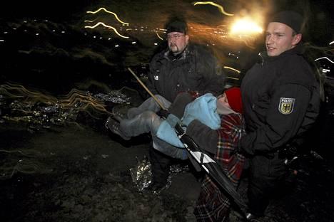 Poliisit kantoivat ydinvoimanvastaisen mielenosoittajan pois kiskoilta Hitzackerissa Saksassa.