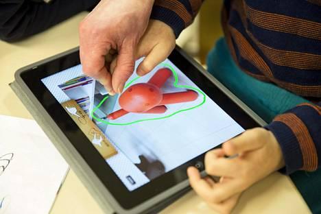 Lapsi opettelee käyttämään iPadia.