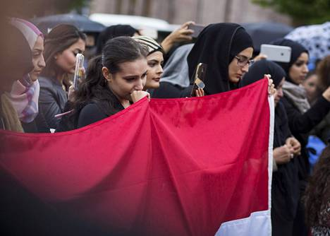 Marjam Al-Aliayat (edessä kesk.) tuli torstaina monen muun tapaan muistamaan Bagdadin sunnuntaisen, lähes 300 uhria vaatineen pommi-iskun uhreja Helsingin Rautatientorille.