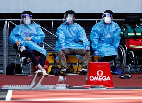 Lääkintähenkilökunta seurasi Tokion olympiastadionilla sunnuntaina järjestettyjä yleisurheilun testikisoja suojavarusteet yllään.