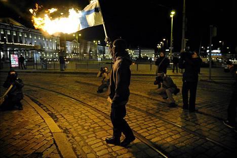 Kuumotuskulkueen mielenosoittaja polttaa Suomen lippua itsenäisyyspäivänä Kauppatorilla Helsingissä 6. marraskuuta 2009. Mielenosoitus oli suunnattu muun muassa Suomen ilmasto- ja ympäristöpolitiikkaa vastaan.