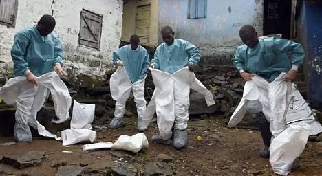 Punaisen Ristin työntekijät pukeutuivat syyskuussa suojavaatteisiin ryhtyessään käsittelemään ebolaan kuolleen ruumista Liberian pääkaupungissa Monraviassa.