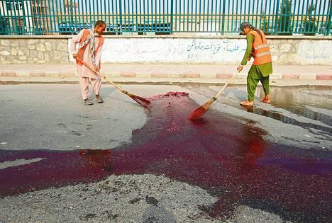 Miehet siivosivat terrori-iskun jälkiä Jalalabadissa 16. heinäkuuta. Polkupyörään asennetun pommin räjähdyksessä kuoli ainakin kaksi siviiliä.
