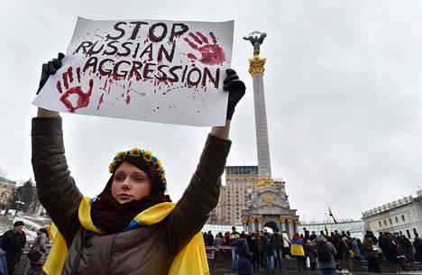 Ukrainan lippuun verhoutunut tyttö kantoi sunnuntaina Kiovan Itsenäisyydenaukiolla kylttiä, jossa Venäjää vaadittiin lopettamaan vihamielisyys.