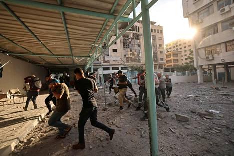 Palestiinalaiset juoksivat suojaan Israelin ilmapommituksilta maanantaina Gazassa.